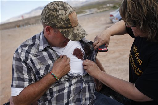 Ammon Bundy ripped Taser hooks from his body and did not back down from police, eventually forcing them to leave. Kriss Thornton (right) tends to his wound. (AP Photo/Las Vegas Review-Journal, John Locher)