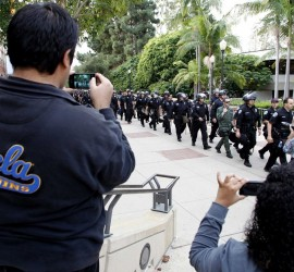 UCLA students take photos as law enforcement in riot gear arrive at the site of the UC Board of Regents meeting in Los Angeles